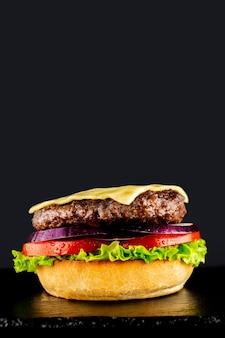 Hamburguesa sabrosa vegetariana fresca sobre un fondo negro. hacer un burguer por etapas