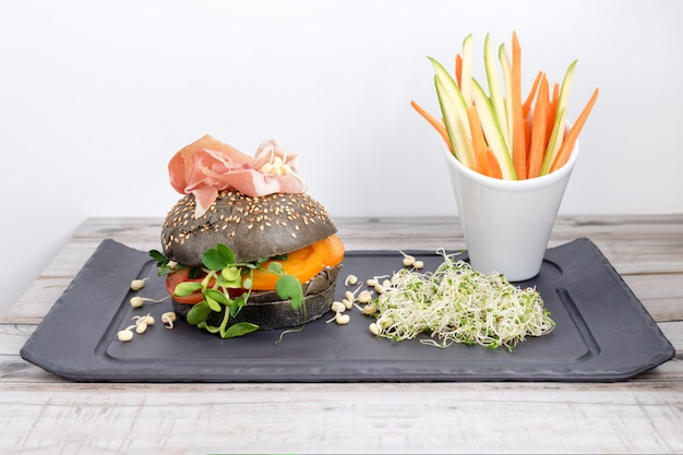 Hamburguesa saludable con jamón, tomates, microgreens y bollos integrales negros, palitos de verduras en pizarra negra sobre la mesa de madera. concepto de comida limpia, dieta, desintoxicación.