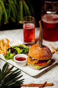 Hamburguesa de ternera con aros de cebolla lechuga con tomate servida con ensalada y papas fritas