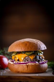 Hamburguesa de ternera artesanal con queso cheddar, tocino, encurtidos, cebolla morada y salsa sobre fondo de madera