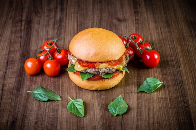 Hamburguesa de ternera artesanal con queso, peperoni italiano, tomate y hojas de albahaca sobre mesa de madera