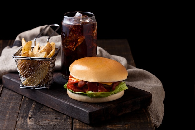 Hamburguesa de ternera fresca con gajos de patata y un vaso de refresco de cola bebida sobre fondo de madera