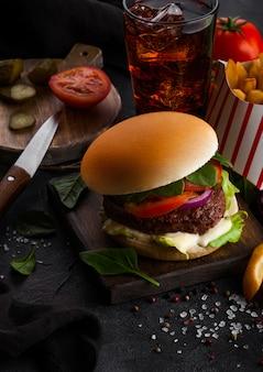 Hamburguesa de ternera fresca con salsa y verduras y vaso de refresco de cola con papas fritas papas fritas en la cocina de piedra.