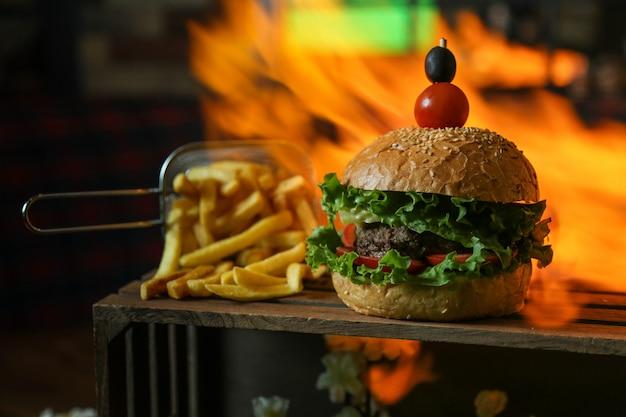 Hamburguesa de ternera lechuga tomate pepino aceitunas papas fritas vista lateral