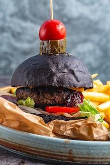 Hamburguesa de ternera negra servida con papas fritas