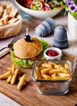 Hamburguesa de ternera servida con canasta de papas fritas