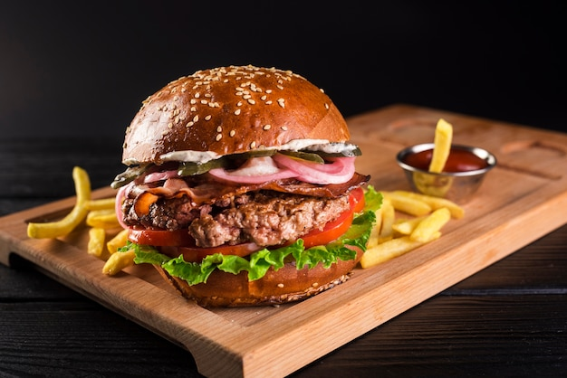 Hamburguesa de ternera sobre una tabla de madera con papas fritas