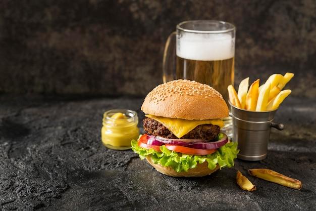 Hamburguesa de ternera vista frontal, papas fritas y salsa con cerveza