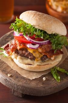 Hamburguesa de tocino y queso con empanada de carne y cebolla de tomate