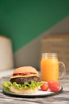 Hamburguesa con tomates y jugo en la mesa