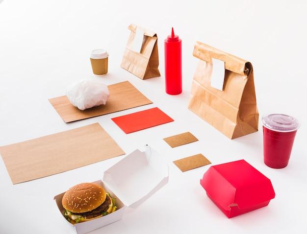 Hamburguesa; vaso desechable; botella de salsa y paquete de comida sobre fondo blanco