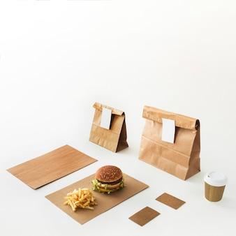 Hamburguesa; vaso desechable; papas fritas y paquete de comida aislado sobre fondo blanco
