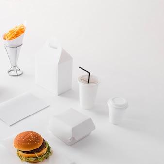 Hamburguesa; vaso desechable; papas fritas y paquete de comida sobre fondo blanco