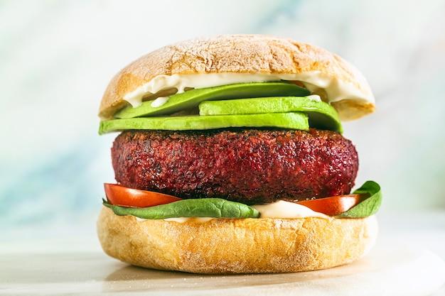 Hamburguesa vegana sin carne con aguacate, tomates y espinacas en la mesa y vino tinto en una copa