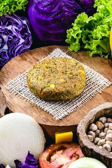 Hamburguesa vegana sin carne elaborada con semillas, verduras, soja, garbanzos, maíz y lichi, rodeada de verduras.