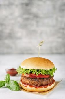 Hamburguesa vegana casera en superficie rústica blanca