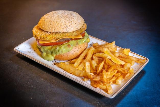 Hamburguesa vegana con guacamole y papas fritas en una placa blanca sobre fondo negro