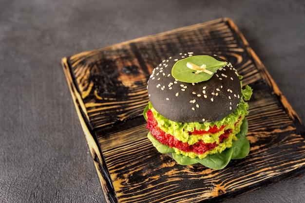 Hamburguesa vegana negra con empanada de aguacate y remolacha
