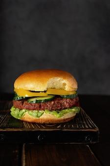 Hamburguesa vegetariana mordida sobre tabla de madera