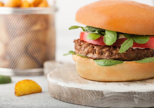 Hamburguesa vegetariana saludable sin carne en una tabla de cortar redonda con verduras sobre un fondo claro con rodajas de patata.