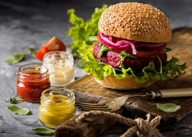 Hamburguesa vegetariana vista frontal en tabla de cortar con salsas
