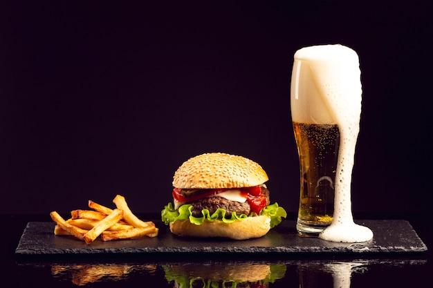 Hamburguesa vista frontal con papas fritas y cerveza