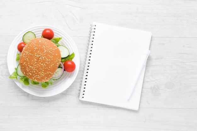 Hamburguesa de vista superior para veganos junto al cuaderno vacío
