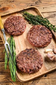 Hamburguesas de bistec de carne molida a la parrilla a la barbacoa, carne picada en una bandeja de madera