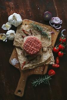 Hamburguesas de carne cruda con hierbas y especias en placa de pizarra oscura