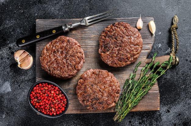 Hamburguesas de carne de ternera a la parrilla a la barbacoa para hamburguesas de carne picada y hierbas sobre una tabla de madera