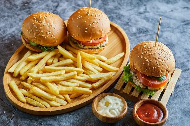 Hamburguesas con patatas fritas en la plancha de madera