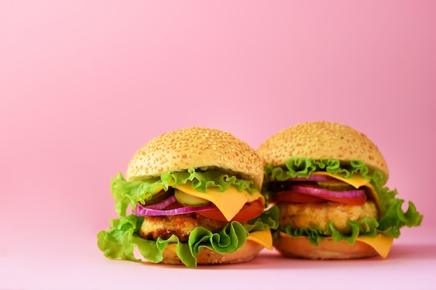 Hamburguesas poco saludables con carne de res, queso, lechuga, cebolla, tomates sobre fondo rosa. comida para llevar. concepto de dieta poco saludable y espacio de copia
