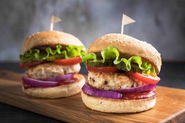 Hamburguesas de pollo caseras con verduras y salsa sobre tabla de cortar de madera