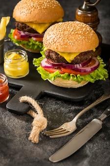Hamburguesas de ternera de alto ángulo con papas fritas, salsa y cubiertos