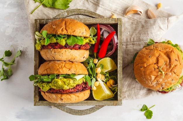 Hamburguesas veganas de remolacha y garbanzos con verduras, guacamole y bollos de centeno en caja de madera. concepto de comida vegana saludable. vista superior, espacio de copia