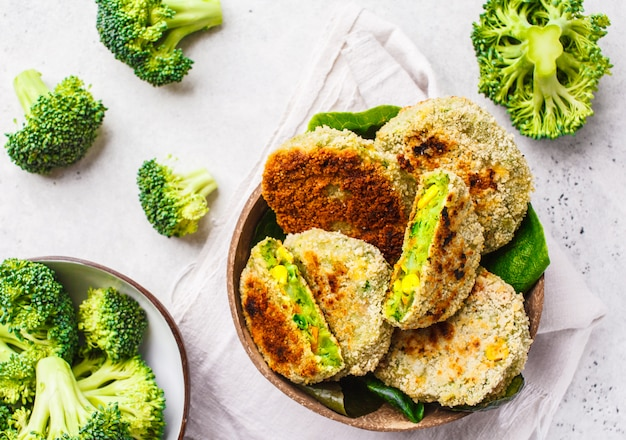 Hamburguesas verdes del bróculi en plato de la cáscara del coco en el fondo blanco, visión superior.