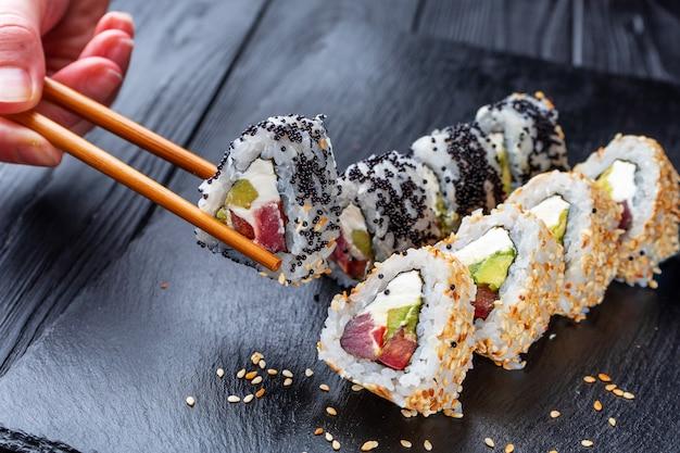Hand with palillos chinos toma sushi de rollos de sushi con queso crema, arroz y salmón en un tablero negro decorado con jengibre y wassabi en una mesa de madera oscura. comida japonesa. enfoque suave selectivo