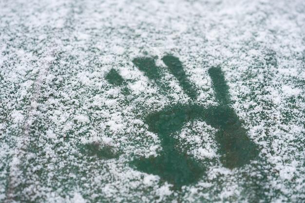 Un handprint en la primera nieve a finales de otoño.