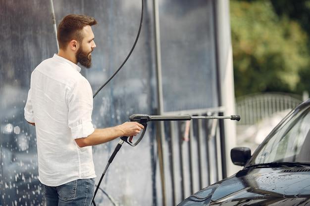 Handsomen hombre en una camisa blanca lavando su auto