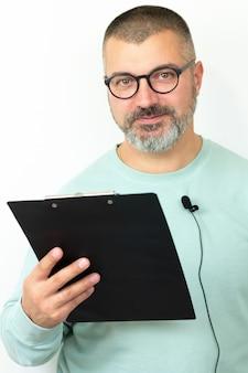 Happt entrenador barbudo empresario con gafas con micrófono y portapapeles.