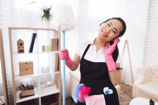 Happy asian maid with mop está escuchando música