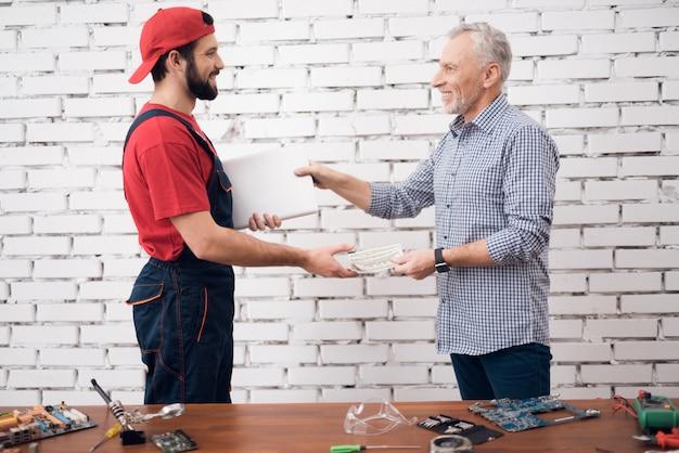 Happy client paga dinero por la reparación de una computadora portátil.