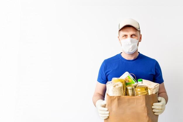 Happy delivery man en gorra azul camiseta en blanco uniforme guante mantenga donaciones bolsa aislado en blanco