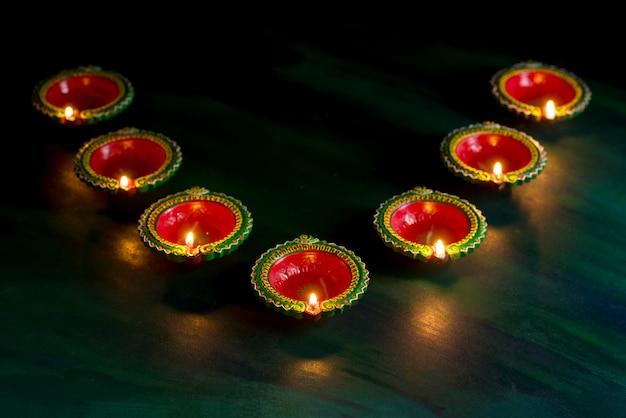 Happy diwali - las lámparas clay diya se encendieron durante la celebración de diwali. diseño de la tarjeta de felicitación del festival hindú de la luz hindú llamado diwali