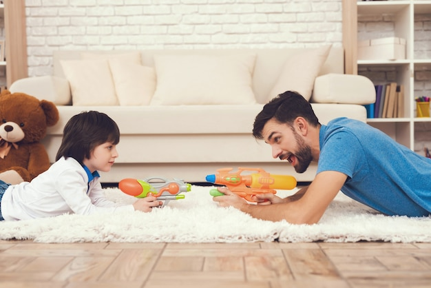 Happy father and sons está jugando con toys gun.
