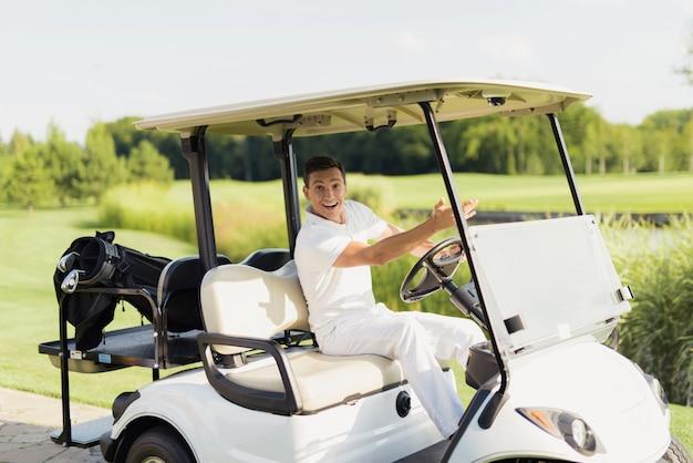 Happy man drives golf car golfista en un campo.