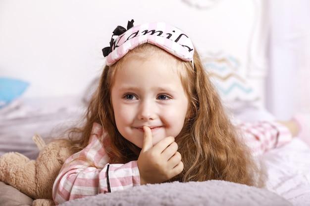 Happy sonrió niña pelirroja está acostada en las sábanas de la cama enorme