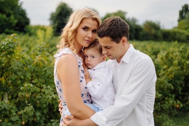 Happy young family dad, mamá e hijo pequeño se ve feliz en el parque