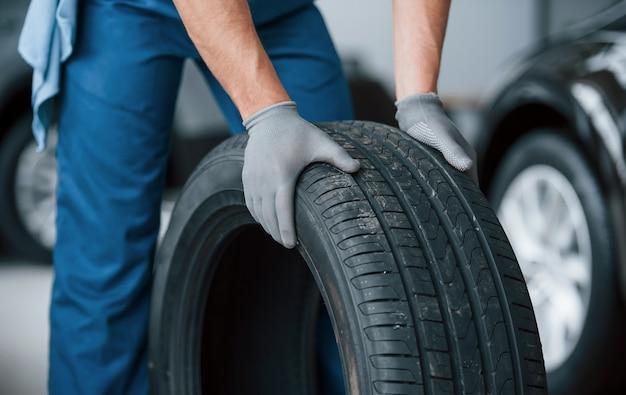Se hará una mejora más y se hará un trabajo. mecánico sosteniendo un neumático en el taller de reparación. reemplazo de neumáticos de invierno y verano
