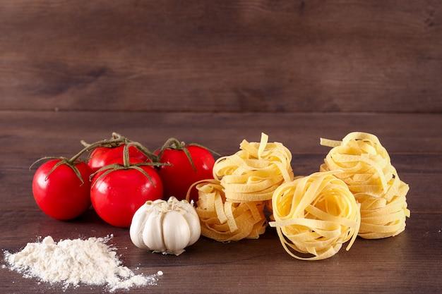 Harina de ajo y pasta de tallarines de tomates cherry rojos frescos sobre superficie de madera
